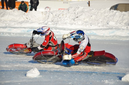 SAMARA, RUSSIA - JANUARY 27: Racing on ice, two unknown driver on a motorcycle with spikes rotates with a large slope on one knee on the ice speedway practice Championship January 27, 2012 in Samara, Russia