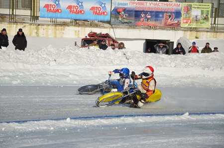 rotates: SAMARA, RUSSIA - JANUARY 29: Racing on ice, two unknown driver on a motorcycle with spikes rotates with a large slope on one knee on the ice speedway Championship January 29, 2012 in Samara, Russia