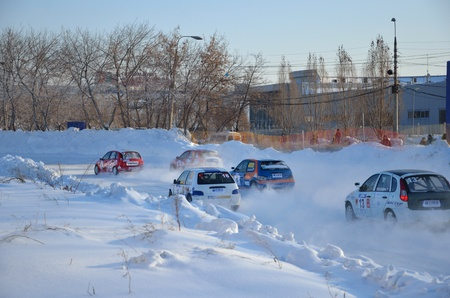 turnabout: RUSSIA SAMARA - FEBRUARU 12: Group of cars compete in the first corner after the start, Cup of Russia in winter track motor racing February 12, 2012 in Samara, Russia