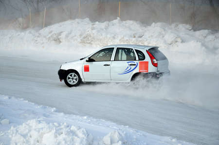turnabout: White car drift adjustment performs on the ice, the winter track racing, shot on the left Stock Photo