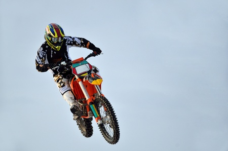 Extreme jump moto racer on the background of clouds the motocross