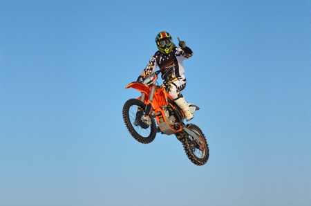 Racer flies on a motorcycle with one hand welcoming the audience, the practice of motocross Samara