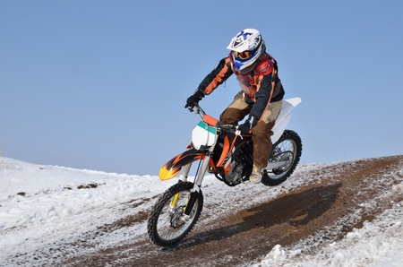 Winter motocross, motorcycle rider flying down the mountain photo