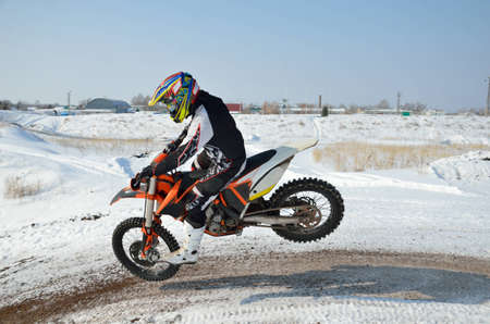 Winter motocross, motorcycle racer lands on front wheel on the snowy slope of the hill