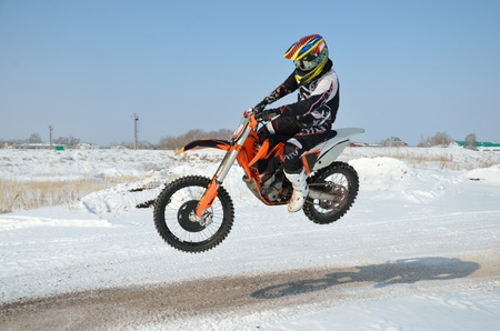 Motocross in the winter, the rider by bike motocross flies sideways over a hill on a snowy road, shot from the left side