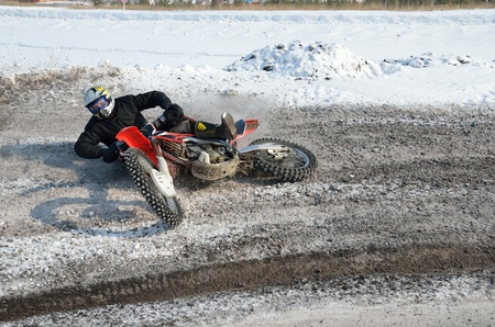 Fall of rider motocross on snow track