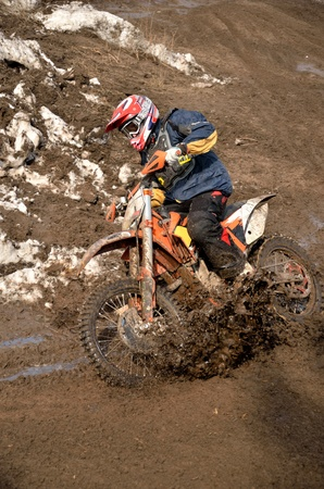 Driver puts the bike in a slanted position, passes a turn on a track with a spray of dirt, the Motocross workout