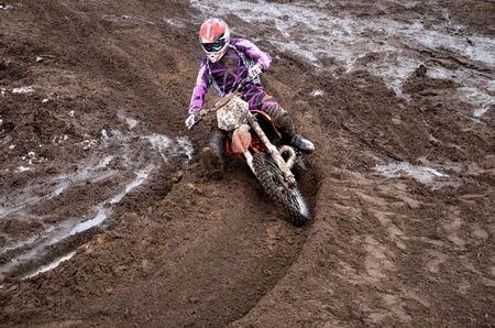 put forward: The driver put the right foot forward at the beginning of a deep rut turning sandy motocross track Editorial