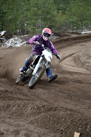 turnabout: Departure with the acceleration out of the left-turn motocross racer, on a sandy road