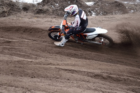 turnabout: Motocross rider veering point-blank of sand with a large plume out from under the rear wheel Stock Photo