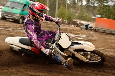 Motocross athlete under helm with a raised leg executes a right turn, on a sand track Stock Photo