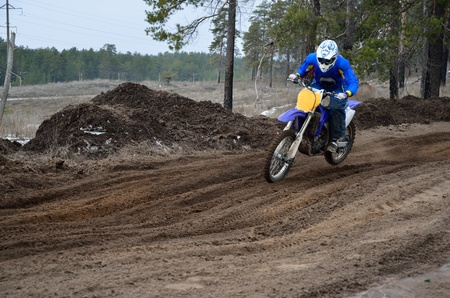 Motorcyclist rides over the sand mounds motocross track on the background of pine forest