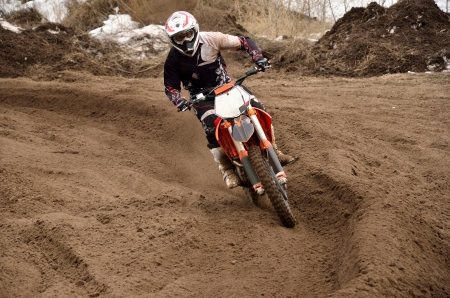 Motocross racing driver at the turning in the deep sandy ruts, shot from the front