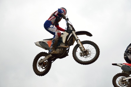 Motocross rider on a motorcycle flying through the air against the sky turning his head photo