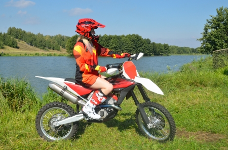 Girl with drawn feet in a red jersey and helmet, sitting on a sport bike for motocross photo