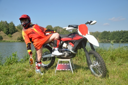 bandwagon: Girl in sports uniform for motocross leaned back standing on one foot, the other placing on the bandwagon motorcycle