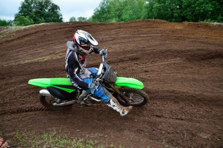 MX rider turns on a dirt hill putting the foot forward photo