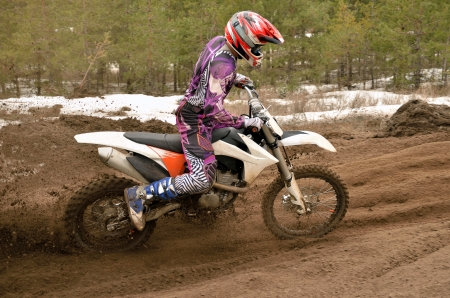 turnabout: MX racer off the corner on the sandy motocross track Stock Photo