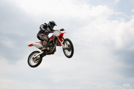 MX rider soaring flight with a turn of the wheel motocross bike, on a background of white clouds