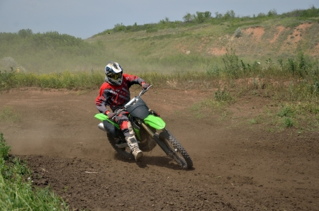 Motocross rider on motorcycle moves cornering track MX photo