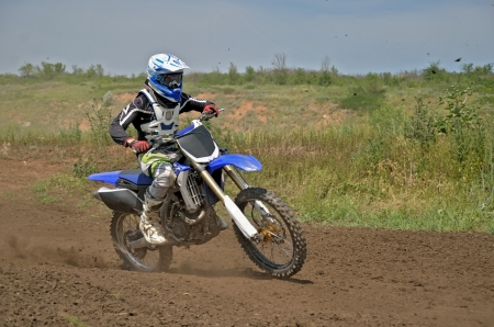MX racer on a motorbike acceleration out bend on track motocross Stock Photo