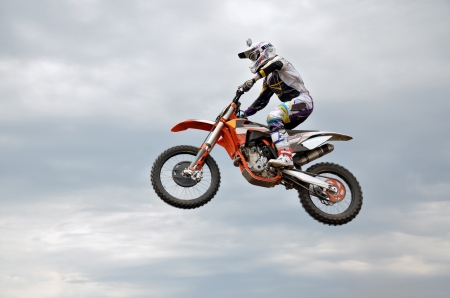 Motocross rider on the motorbike performs efficient flight is hanging in the open air
