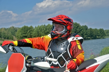 'rig out': Motocross rider in the form and helmet, the motorcycle near Stock Photo