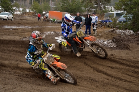 swerve: Two riders MX 100 E. Rekshin, 31 N. Misyulya compete in turning, on a sandy track ruts, the Motocross practice April 8, 2012 in Samara, Russia Editorial