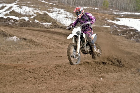 cornering: MX rider on a motorcycle rides cornering along the sandy furrow motocross track