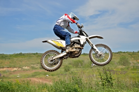 Motocross rider on a motorcycle in the air against the sky and mountains  Stock Photo