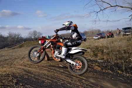 Biker rides the top of earthen the hill motocross tracks