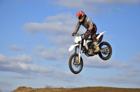 Flight of motorcycle racer motocross forward inclined against the blue sky and clouds photo