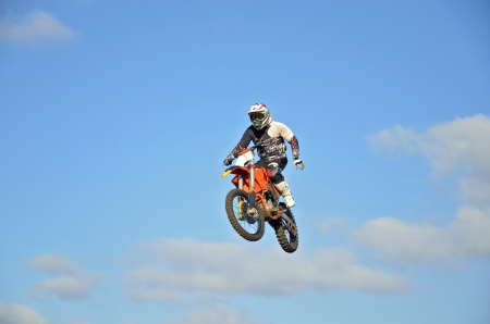 Motocross rider high in the air on a motorcycle one-hand control, against the blue sky and clouds photo