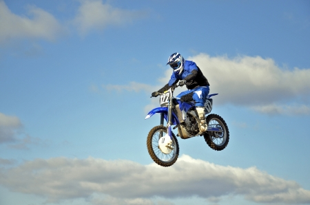 High flight of motorcycle racer motocross forward inclined against the blue sky and clouds