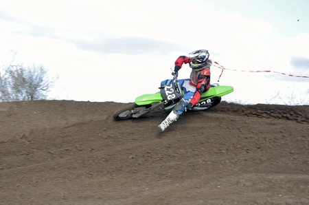 turnabout: Motocross biker rides on an inclined plane of rotation