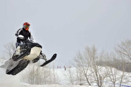 On the snowmobile rider flies out the hillock of snow sideways Stock Photo
