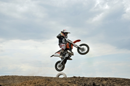 sharply: RUSSIA, SAMARA � MAY 6:  A boy I. Gavrilov on a small motorcycle takes off MX jumping sharply up, the 50 sm3 class the Regional Motocross Championship on May 6, 2012 in Samara, Russia Editorial