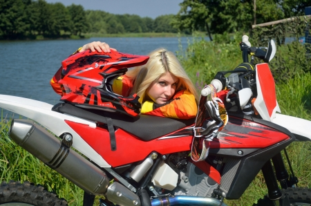 Girl with blond hair is standing, leaned on the motorbike for motocross, put a hand on a helmet photo