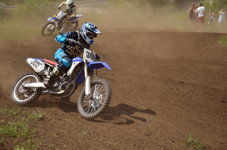 turnabout: RUSSIA, SAMARA - JUNE 16: Motocross rider N. Bereskev on the motorcycle is accelerating at the exit of a turn, with a large rear wheel slip, the class Open Regional Motocross on June 16, 2012 in Samara, Russia