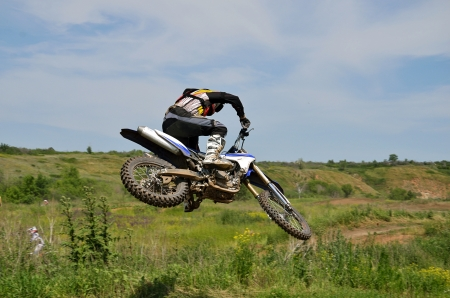 Extreme jump motocross racer by motorcycle, shot right rear Stock Photo