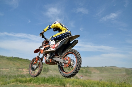 A rider by motorcycle MX flies over the hill against the blue sky, shot behind - the left side photo