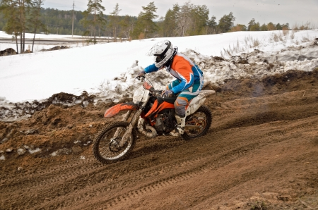 MX racer rides a motorcycle going down the motocross track of snow and sand photo