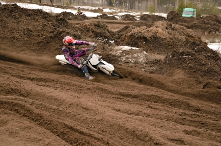 Motocross racer, with a large slope in gritty point-blank rotates on the motorcycle