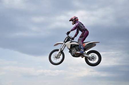 mx: High jump MX racer on a motorcycle, on a cloudy sky