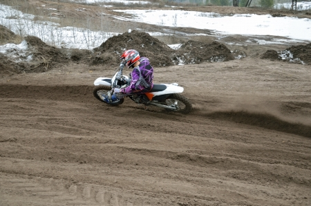 turnabout: Motocross rider, veering point-blank of sand with a large plume out from under the rear wheel