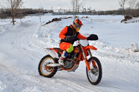 turnabout: racer on a motorcycle rides with the demolition of the rear wheel on the snow-covered road in the reversal