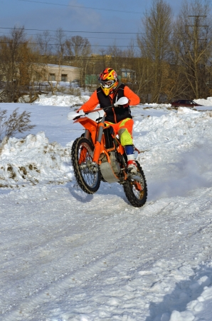 Winter motocross rider rides on the rear wheel on the snow-covered road photo
