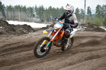 racer on a motorcycle shoots out of a turn, on a sandy track Stock Photo