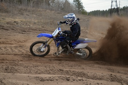 MX racer on a motorcycle accelerated along a sandy the track, motocross photo