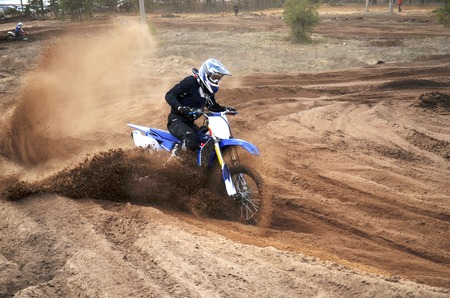 Motorcycle rider bogged down in loose sand on a steep bend motocross track